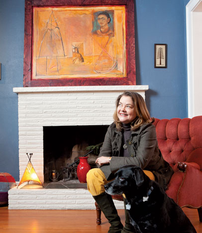 Frances McCue (with pal Ida) fills her home with Moroccan art, such as the large painting by Mohammed Daoudi, and the small henna tree, by Zini